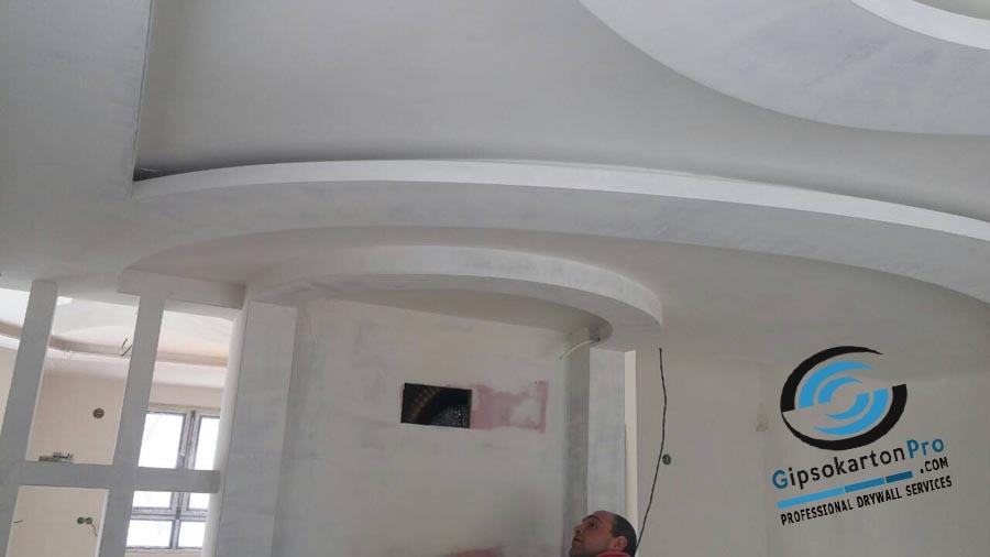 Окачени тавани за хол . Извити бордове за скрито осветление и фигури от гипсокартон